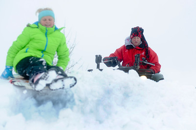Ian Maule - For Shaw Media Hailey Bullamore ,11, sleds down a pile of snow while her father, Brett, both of Johnsburg, Il uses a four wheeler to plow his driveway Sunday morning ,Decemeber 22,2013, in Johnsburg,Il. McHenry County got between 3-6 inches of snow starting last night and into the morning.