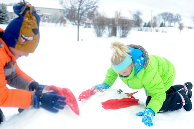Ian Maule - For Shaw Media  Garrett,8, and Hailey Bullamore,11, both of Johnsburg,Il., build snowmen in their front yard Sunday morning ,Decemeber 22,2013, in Johnsburg,Il. McHenry County got between 3-6 inches of snow starting last night and into the morning.