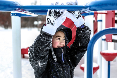 Sarah Nader- snader@shawmedia.com Skyler Davison, 10, of Lake in the Hills crosses the money bars while playing at Ted Spella Community Park in Algonquin after sledding with his family Thursday, December 26, 2013.