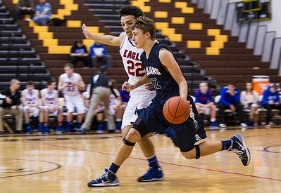 Kyle Grillot - kgrillot@shawmedia.com   Cary-Grove senior Jason Gregoire (12) dribbles up the court, defended by Lakes junior Tramone Hudson (22) during the third quarter of the semifinal match Friday at the Hinkle Holiday Classic at Jacobs in Algonquin. Cary-Grove won, 49-34.