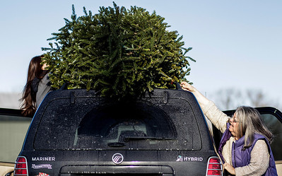 Kyle Grillot - kgrillot@shawmedia.com   Becky McTague of Cary (right) helps her daughter Rachael unload their Christmas tree to be recycled at the Algonquin Township Headquarters Saturday in Cary. Through the McHenry County Conservation District, trees are being accepted until January 31 at the following three locations; Rush Creek Conservation Area, Algonquin Township Headquarters and Glacial Park. Trees are then processed into mulch, which will be available free of charge at a later date.