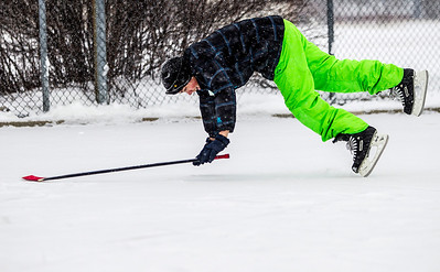 Kyle Grillot - kgrillot@shawmedia.com   Miguel Lopez, 13, of Algonquin catches his fall after slipping while playing hockey with his brother at Willoughby Farms Park Tuesday in Algonquin.