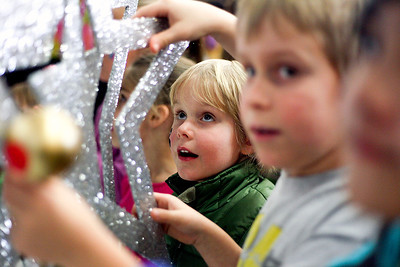 Sarah Nader- snader@shawmedia.com Kyle Bohrnell (center), 5, of Woodstock grabs onto a glittered star cut out as its lowered to the ground during a countdown to noon at the 5th annual Kids Bash at Crosby Elementary School in Harvard Tuesday, December 31, 2013. Children celebrated New Year's Eve with games, crafts, face painting, music and a countdown to noon with Mayor Jay Nolan.