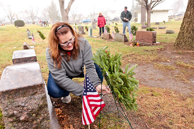 Michelle LaVigne/ For Shaw Media Volunteer Danielee Kratz of McHenry, secures a wreath with a zip tie after it's placement on a  grave of a veteran at St. Mary of the Assumption Church cemetery in McHenry, Ill.  on Saturday December 12, 2015 in conjunction with the wreaths across America program.