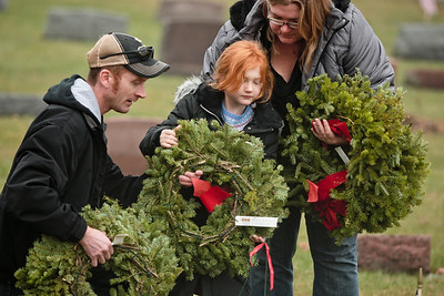 Michelle LaVigne/ For Shaw Media Volunteers seven-year-old McKenna Arnold, her father Ken and mother Charlesa of McHenry place a wreath on a grave of a veteran inside of St. Mary of the Assumption Church cemetery in McHenry, Ill.  on Saturday December 12, 2015 in conjunction with the wreaths across America program.