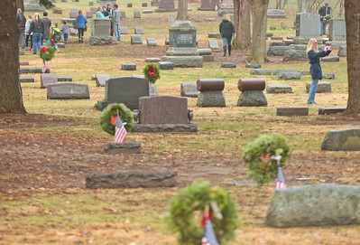Michelle LaVigne/ For Shaw Media Volunteers place wreaths on the graves of veterans at St. Mary of the Assumption Church and Woodlawn cemetery in McHenry, Ill.  on Saturday December 12, 2015 in conjunction with the wreaths across America program.
