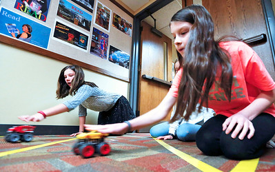 """John Konstantaras - For Shaw Media Lundahl Middle School sixth grader Maddie Zilm (left) and Prairie Grove Junior High seventh grader Sage Brossard,  use toy cars for a graphing project during a mentoring session for the """"Stem is Fair Game"""" Science Fair at the Crystal Lake Library on Saturday, December 3, 2016 in Crystal Lake."""