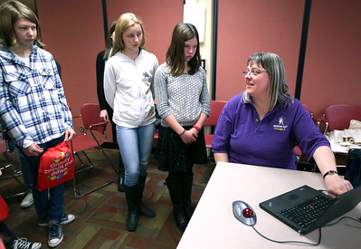 """John Konstantaras - For Shaw Media Lorrie-Ann Fisher, from Crystal Lake, a technical service specialist with Morton Salt, talks with girls about graphs during a mentoring session for the """"Stem is Fair Game"""" Science Fair at the Crystal Lake Library on Saturday, December 3, 2016 in Crystal Lake."""