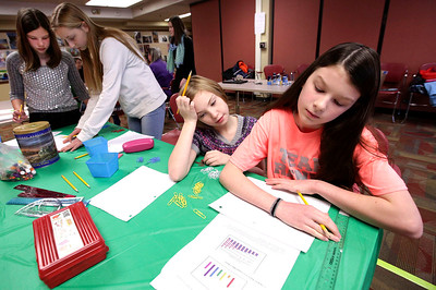 John Konstantaras - For Shaw Media Lundahl Middle School sixth grader Maddie Zilm (from left) Hannah Beardsley Middle School seventh grader Kennedy Mark and Prairie Grove Junior High School seventh graders Ali Sindberg and Sage Brossard work on a graphing project during a mentoring session for the Stem is Fair Game Science Fair at the Crystal Lake Library on Saturday, December 3, 2016 in Crystal Lake.