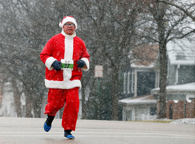 Jim Kingsberg runs down Brink St during the 1 mile run in the 5th annual Santa Run on Sunday, December 4, 2016 in Crystal Lake. The run benefits Kiwanis Club of Crystal Lake, Turning Point, CASA, Girls on the Run of NW IL, Big Brothers Big Sisters, and Main Stay Therapeutic Riding. John Konstantaras photo for the Northwest Herald