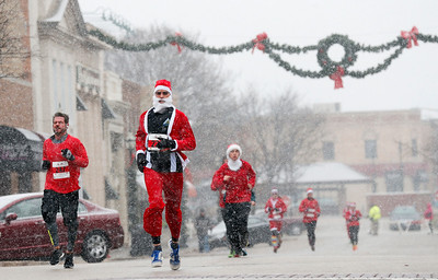 Rob Wolf, center, runs down Williams St as runners head toward the finish line of the 5k run in the 5th annual Santa Run on Sunday, December 4, 2016 in Crystal Lake. The run benefits Kiwanis Club of Crystal Lake, Turning Point, CASA, Girls on the Run of NW IL, Big Brothers Big Sisters, and Main Stay Therapeutic Riding. John Konstantaras photo for the Northwest Herald