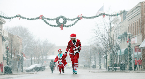 Jennifer Tabor and her 5-year-old daughter Colleen, from Crystal Lake, run down Williams St. as they head for the finish of the 5k run in the 5th annual Santa Run on Sunday, December 4, 2016 in Crystal Lake. The run benefits Kiwanis Club of Crystal Lake, Turning Point, CASA, Girls on the Run of NW IL, Big Brothers Big Sisters, and Main Stay Therapeutic Riding. John Konstantaras photo for the Northwest Herald