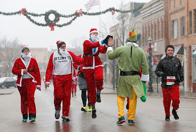 Devin Frank, from Crystal Lake, jumps as she high fives Chris Christensen, from Cary, as they head toward the finish line of the 5k run during the 5th Annual Santa Run on Sunday, December 4, 2016 in Crystal Lake. The run benefits Kiwanis Club of Crystal Lake, Turning Point, CASA, Girls on the Run of NW IL, Big Brothers Big Sisters, and Main Stay Therapeutic Riding. John Konstantaras photo for the Northwest Herald