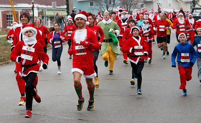 Gonzalo Gomez (685) runs down Williams St. with a pack of Santas during the 5k run of the 5th annual Santa Run on Sunday, December 4, 2016 in Crystal Lake. The run benefits Kiwanis Club of Crystal Lake, Turning Point, CASA, Girls on the Run of NW IL, Big Brothers Big Sisters, and Main Stay Therapeutic Riding. John Konstantaras photo for the Northwest Herald