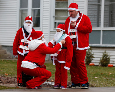 Tyler Lodewyck, 10, left from Lake in the Hills, and Bryan Lodewyck, right, wait as Karen Lodewyck, helps her daughter Ava, 8 with her Santa costume as the family gets ready for their first Santa Run on Sunday, December 4, 2016 in Crystal Lake. The run benefits Kiwanis Club of Crystal Lake, Turning Point, CASA, Girls on the Run of NW IL, Big Brothers Big Sisters, and Main Stay Therapeutic Riding. John Konstantaras photo for the Northwest Herald