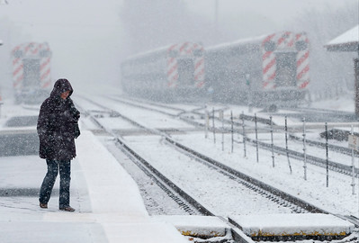Ann Wells, from Crystal Lake, crosses the Metra tracks in the snow to catch a train to Chicago on Sunday, December 4, 2016 in Crystal Lake.  John Konstantaras photo for the Northwest Herald