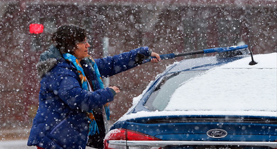 Laura Rosinski, from Marengo, clears snow off her car in the Metra Parking lot on Sunday, December 4, 2016 in Crystal Lake.  John Konstantaras photo for the Northwest Herald