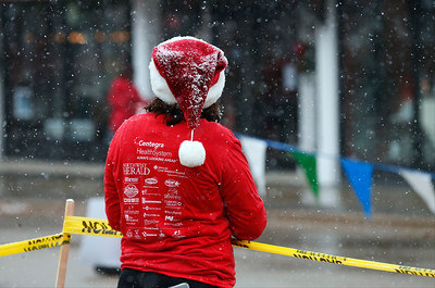 Alicia Cronkite, from McHenry, stands int he snow as she waits for runners at the finish line of the Santa Run on Sunday, December 4, 2016 in Crystal Lake.  John Konstantaras photo for the Northwest Herald