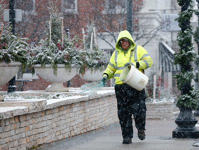 Ricardo Gonzalez, from Carpentersville spreads salt on the sidewalk along Williams St as the snow falls on Sunday, December 4, 2016 in Crystal Lake.  John Konstantaras photo for the Northwest Herald
