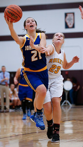Aannah Interrante (21) of Johnsburg drives past Mackenzie Hahn (23) of Richmond-Burton during the fourth quarter of their game at Richmond-Burton High School  on Tuesday, December 6, 2016 in Richmond. The Skyhawks defeated the Rockets 40-24. John Konstantaras photo for the Northwest Herald