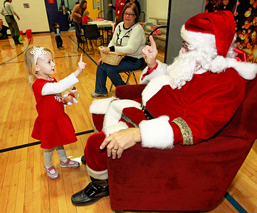Candace H. Johnson-For Shaw Media Delaney Cullen, 3, of Lake Villa talks with Santa during the Milk-N-Cookies with Santa event at the Round Lake Area Park District in Round Lake.
