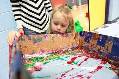 Candace H. Johnson-For Shaw Media Natalie Englund, 2, of Round Lake Beach stays close to her mother, Amanda, as she paints a picture with a marble ball during the Milk-N-Cookies with Santa event at the Round Lake Area Park District in Round Lake.