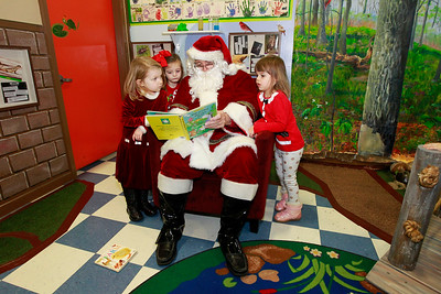 Candace H. Johnson-For Shaw Media Ginger Bird, of Round Lake, Kensington Kiely and Lulu Paulus, both of Grayslake, all 4, read a book with Santa during the Milk-N-Cookies with Santa event in the Children's Neighborhood Museum at the Round Lake Area Park District in Round Lake.