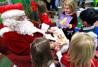 "Candace H. Johnson-For Shaw Media Ginger Bird, 4, of Round Lake shows Santa a book called, ""Ten Little Fingers,"" during the Milk-N-Cookies with Santa event in the Children's Neighborhood Museum at the Round Lake Area Park District in Round Lake."