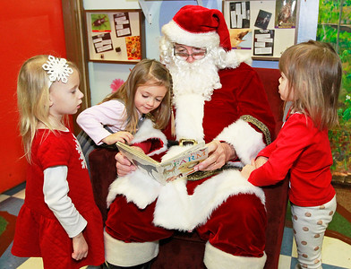 Candace H. Johnson-For Shaw Media Delaney Cullen, of Lake Villa, Aubree Hunt, of Antioch, both 3, and Lulu Paulus, 4, of Grayslake listen to Santa read a book during the Milk-N-Cookies with Santa event in the Children's Neighborhood Museum at the Round Lake Area Park District in Round Lake.