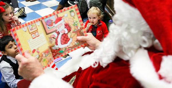 Candace H. Johnson-For Shaw Media Krish Chatlani, of Gurnee, Kensington Kiely, of Grayslake, both 4, and Parker Danitz, 2, of McHenry eat some cookies while listening to Santa read a holiday book during the Milk-N-Cookies with Santa event in the Children's Neighborhood Museum at the Round Lake Area Park District in Round Lake.