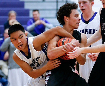 James Queen (right) of Prairie Ridge and Isaiah Gonzales (30) of Hampshire battle for a ball during the second quarter of their game at Hampshire High School on Wednesday, December 7, 2016 in Hampshire. The Wolves defeated the Whip-Purs 55-38. John Konstantaras photo for the Northwest Herald