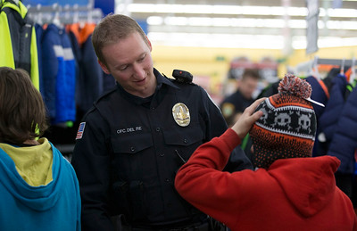 Johnsburg police officer Kevin Del Re helps some boys look for a hat during the Shop With A Cop event at Walmart on Sunday December 11, 2016 in Johnsburg. John Konstantaras photo for the Northwest Herald
