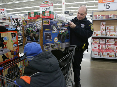 Chief Ciro Cetrangolo, with the Richmond Police Department, helps a kids out with a toy during the Shop With A Cop event at Walmart on Sunday December 11, 2016 in Johnsburg. John Konstantaras photo for the Northwest Herald