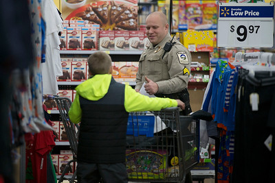 Sgt. Steve Johnson, with the McHenry County Conservation District , helps during the Shop With A Cop event at Walmart on Sunday December 11, 2016 in Johnsburg. John Konstantaras photo for the Northwest Herald