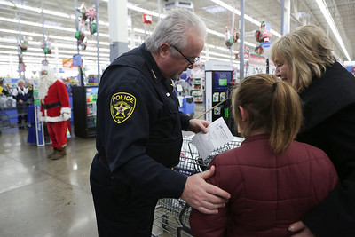 Lakemoor Chief of Police David Dodlewski, looks over a shopping list with Kendall during the Shop With A Cop event at Walmart on Sunday December 11, 2016 in Johnsburg. John Konstantaras photo for the Northwest Herald
