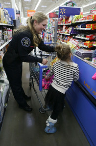 Officer Danielle Stevens, with McHenry County College, helps Eliza check out during the Shop With A Cop event at Walmart on Sunday December 11, 2016 in Johnsburg. John Konstantaras photo for the Northwest Herald