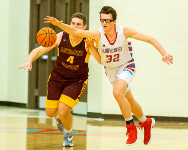 Marion Central Catholic's Sam Ohlrich (32) and Richmond Burton defender Joey St.Pierre (4) go for a loose ball Tuesday, Dec. 13 2016 at Marion Central High School in Woodstock. Marion went on to win 60-35.