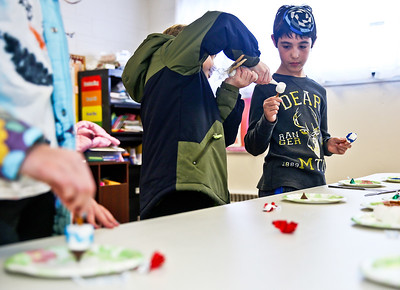 Michelle LaVigne/ For Shaw Media Nine-year-old Charlie Shuman-Lysen of Huntley helps 10-year-old Hunter Purvin of Crystal Lake decorate his marshmallow dreydal while attending the McHenry County Jewish Congregation's Community Chanukah Celebration on Sunday, December 18, 2016 at the McHenry County Jewish Congregation in Crystal Lake.