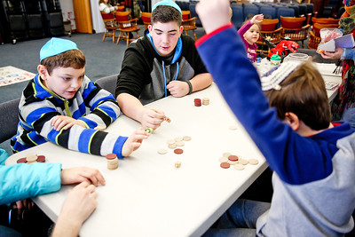 Michelle LaVigne/ For Shaw Media Nine-year-old Andrew Kelly of Huntley (right,) celebrates a successful spin of the dreidel while playing with 12-year-old Josh Bluver of Lake in the Hills (left,) and 14-year-old Zach Cottingham of Algonquin. The McHenry County Jewish Congregation hosted a Community Chanukah Celebration on Sunday, December 18, 2016 at the McHenry County Jewish Congregation in Crystal Lake which included music, games and food.