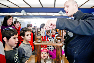 Michelle LaVigne/ For Shaw Media Rabbi Tom Samuels of Chicago prepares to light menorah in front of (closest left,) ten-year-old brothers Hunter and Miles Purlin of Crystal Lake, three-year-old Nava Bessemer of Gilberts and the other participants of the McHenry County Jewish Congregation's Community Chanukah Celebration on Sunday, December 18, 2016 at the McHenry County Jewish Congregation in Crystal Lake.