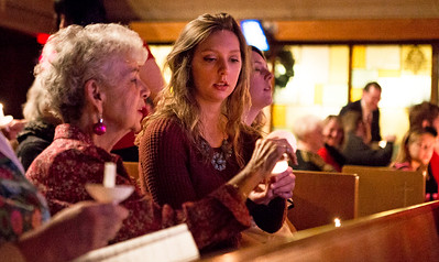 Mike Greene - For Shaw Media  Krista Seibt, right of McHenry, passes candlelight to Carole Bellino, of Florida, during St. Paul's United Church of Christ's annual Christmas Eve Candlelight Worship Services Saturday, December 24, 2016 in Crystal Lake. The 5 p.m. Family Worship Service included performances by the Connection Youth Choir with the Adult Choir performing during the traditional 11 p.m. worship service.