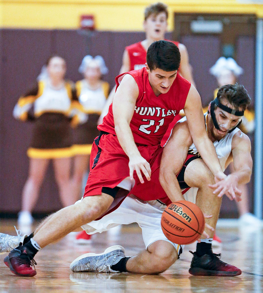 Andrew Fulcer (21) from Huntley and Daniel Murray (23) from Jacobs battle for a loose ball during the second quarter of their game at Jacobs High School  on Wednesday, December 13, 2017 in Algonguin, Illinois. The Golden Eagles defeated the Red Raiders 58-37. John Konstantaras photo for Shaw Media