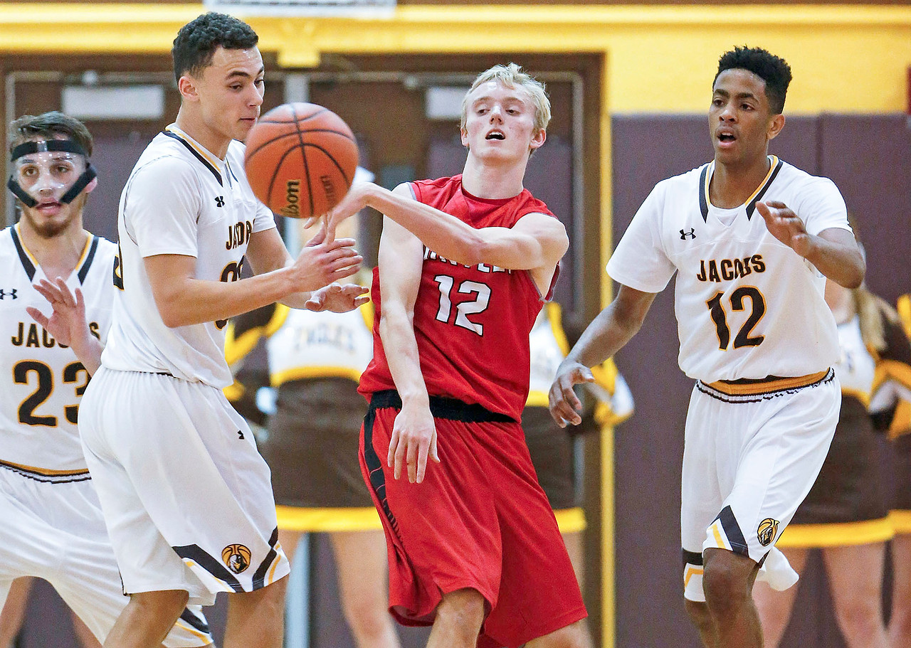 Cory Knipp (12) from Huntley passes the ball around Nikolas Balkcom (33, left) from Jacobs during the second quarter of their game at Jacobs High School  on Wednesday, December 13, 2017 in Algonguin, Illinois. The Golden Eagles defeated the Red Raiders 58-37. John Konstantaras photo for Shaw Media