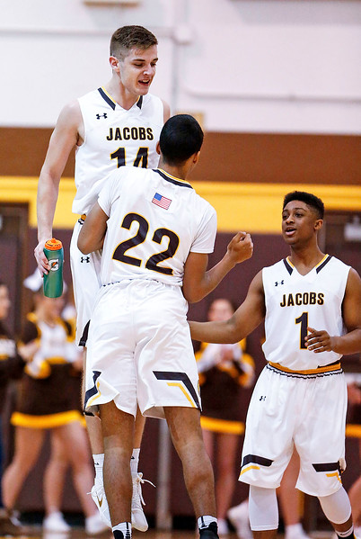 Ryan Phillips (14, left) greets Jaden Henderson (22) from Jacobs after his shot at the buzzer to end the third quarter of their game against Huntley at Jacobs High School  on Wednesday, December 13, 2017 in Algonguin, Illinois. The Golden Eagles defeated the Red Raiders 58-37. John Konstantaras photo for Shaw Media