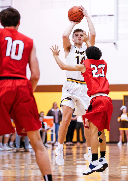 Ryan Phillips (14) from Jacobs shoots a basket over Ryan Crosby (23) from Huntley during the first quarter of their game at Jacobs High School  on Wednesday, December 13, 2017 in Algonguin, Illinois. The Golden Eagles defeated the Red Raiders 58-37. John Konstantaras photo for Shaw Media