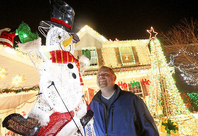 "Candace H. Johnson-For Shaw Media Tim Herzog looks up at a bright snowman on the top of a stack of snowmen he put in his Christmas lights display in the front yard of his family's ""Christmas House"" in Round Lake. It took Herzog forty-seven hours to put up the display. (12/15/17)"