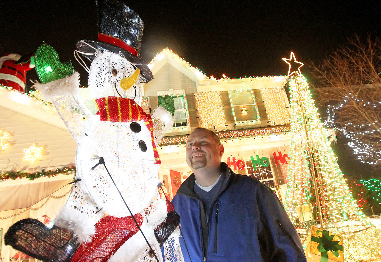 """Candace H. Johnson-For Shaw Media Tim Herzog looks up at a bright snowman on the top of a stack of snowmen he put in his Christmas lights display in the front yard of his family's """"Christmas House"""" in Round Lake. It took Herzog forty-seven hours to put up the display. (12/15/17)"""