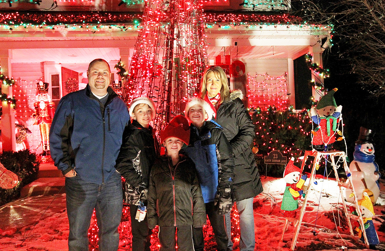 """Candace H. Johnson-For Shaw Media Tim and Cindy Herzog with their children, Tyler and his twin bother, John, both 11, and Peyton, 7, (in the middle) in the front yard of their decorated """"Christmas House"""" in Round Lake.(12/15/17)"""