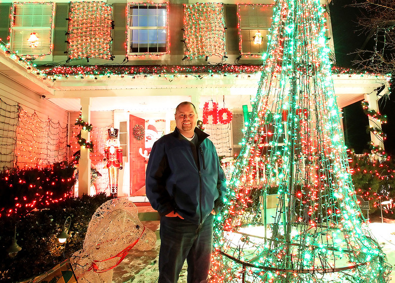 """Candace H. Johnson-For Shaw Media Tim Herzog stands in the front yard of his family's """"Christmas House"""" at night in Round Lake.The lights go on at 5pm. and go off at 10:00 pm. and will stay up until a week after Christmas.(12/15/17)"""