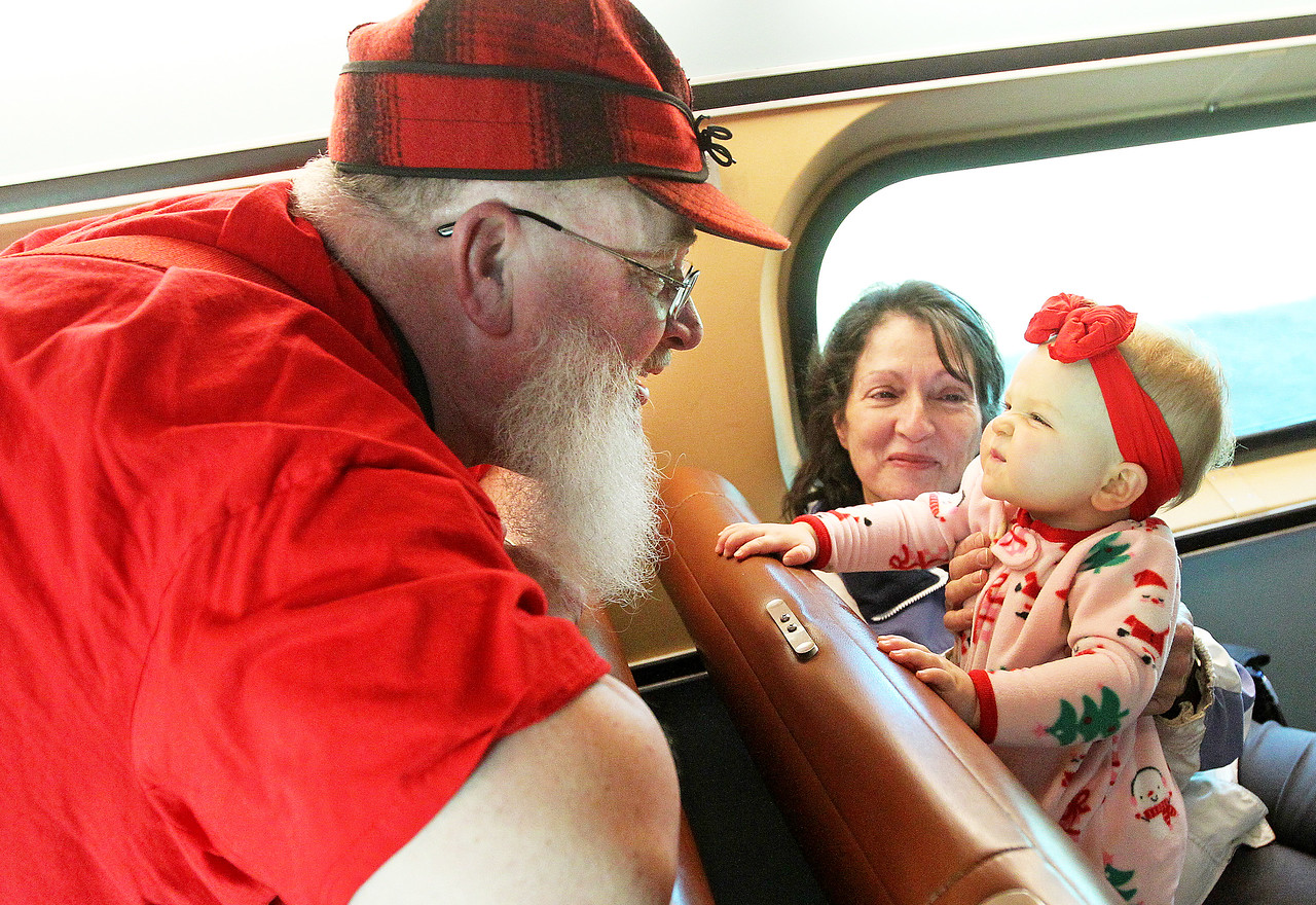 Candace H. Johnson-For Shaw Media Santa visits with Mary Deutsch and her granddaughter, Ali Sheeks, 1, both of Burlington, Wis., as they head home from the North Pole on a Metra train during Antioch's North Pole Express Train event.(12/19/17)